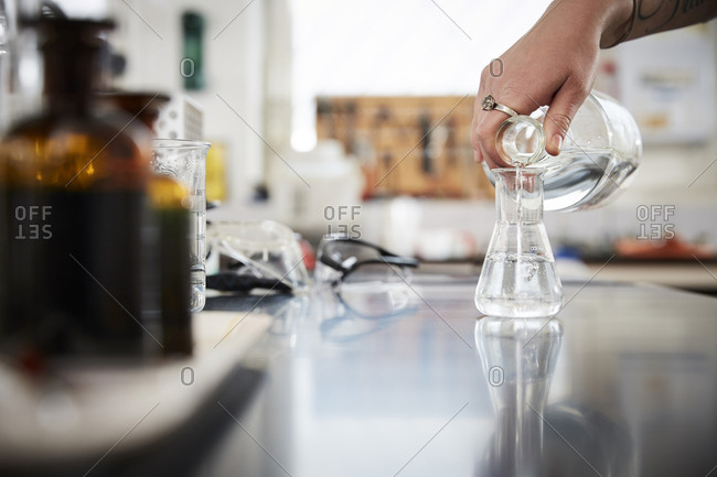 Cropped hand of female student pouring liquid solution in flask from bottle at laboratory