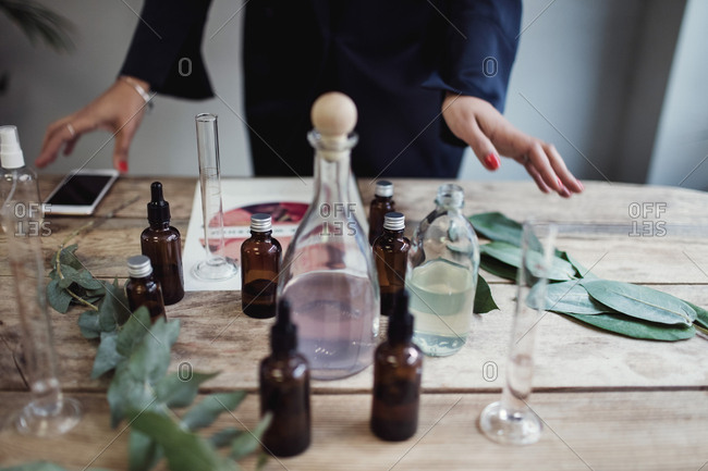 Midsection of mid adult female entrepreneur preparing perfume on table at workshop