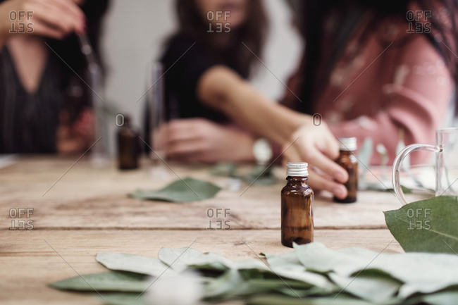 Midsection of female colleagues preparing perfume at table in workshop