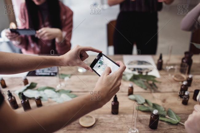Cropped hand of woman photographing perfume bottles on table at workshop