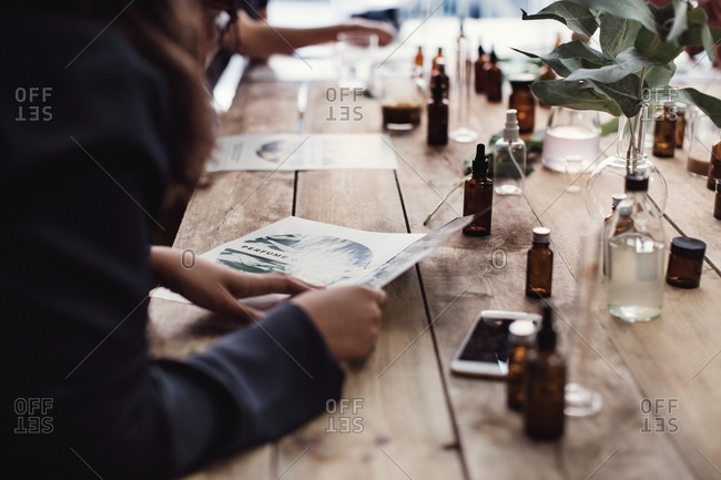 Midsection of woman reading brochure by perfume bottles at table in workshop