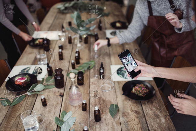 Cropped hand of woman photographing table by female colleague standing at perfume workshop