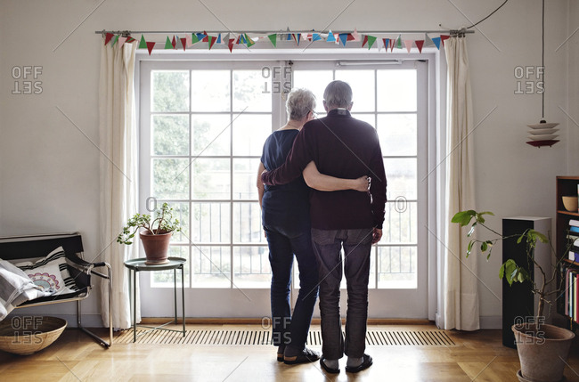 Full length rear view of retired couple looking through window at home