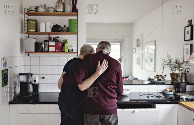 Rear view of retired senior couple standing in kitchen at home