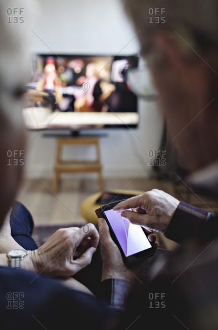 Senior couple sitting with mobile phone watching TV at home