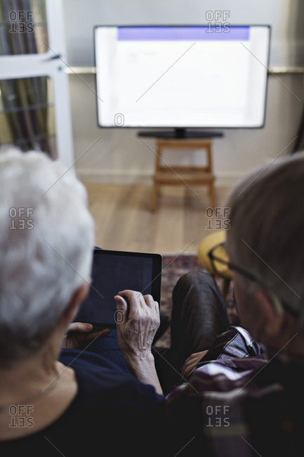 Rear view of senior couple sitting with digital tablet watching TV at home