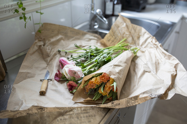 High angle view of flower bouquet on wrapping paper in kitchen