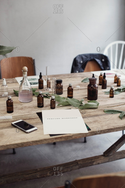 High angle view of mobile phone and brochure by perfume bottles on wood table at workshop