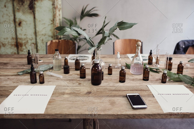 High angle view of mobile phone amidst perfume bottles on table at workshop