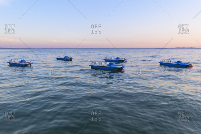 Garda, Veneto, Italy - August 12, 2016: Lake Garda (Lago di Garda) with anchored pedal boats at dusk