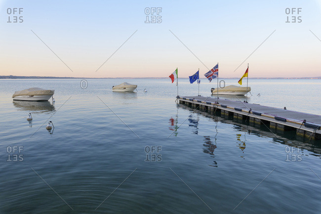 Bardolino, Veneto, Italy - August 14, 2016: Covered, motorboats docked at jetty at dawn on Lake Garda (Lago di Garda)