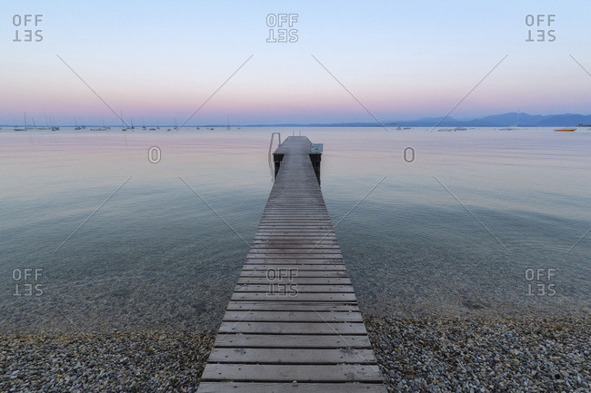 Bardolino, Veneto, Italy - August 14, 2016: Wooden jetty on Lake Gardo (Lago di Garda) at dawn