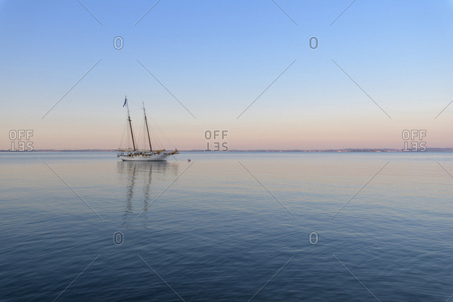 Bardolino, Veneto, Italy - August 14, 2016: Two masted sailboat anchored on Lake Garda (Lago di Garda) at dawn