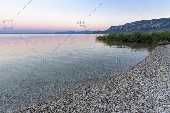 Close-up of shoreline at Lake Garda (Lago di Garda) at dawn in Garda in Veneto, Italy