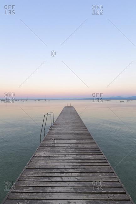 Wooden jetty on Lake Gardo (Lago di Garda) at dawn in Bardolino in Veneto, Italy