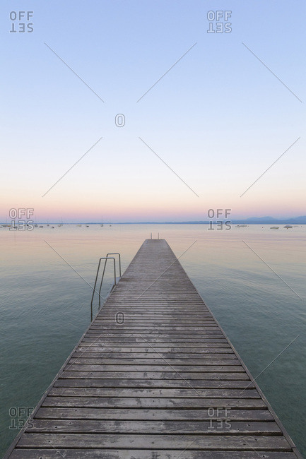 Wooden jetty on Lake Gardo (Lago di Garda) at dawn in Bardolino in Veneto, Italy