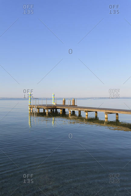 Wooden jetty on Lake Garda (Lago di Garda) in the morning at Bardolino in Veneto, Italy