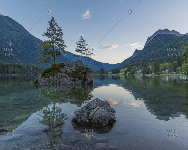 Lake Hintersee with mountains and trees growing on small, rock island at dawn at Ramsau in the Berchtesgaden National Park in Upper Bavaria, Bavaria, Germany