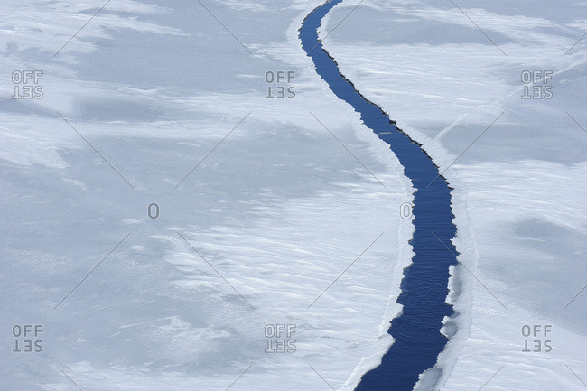 Elevated view of a large crack in pack ice at Snow Hill Island on the Weddel Sea on a sunny day at the Antarctic Peninsula, Antarctica