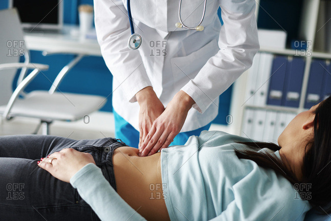Doctor examining woman's stomach in medical practice