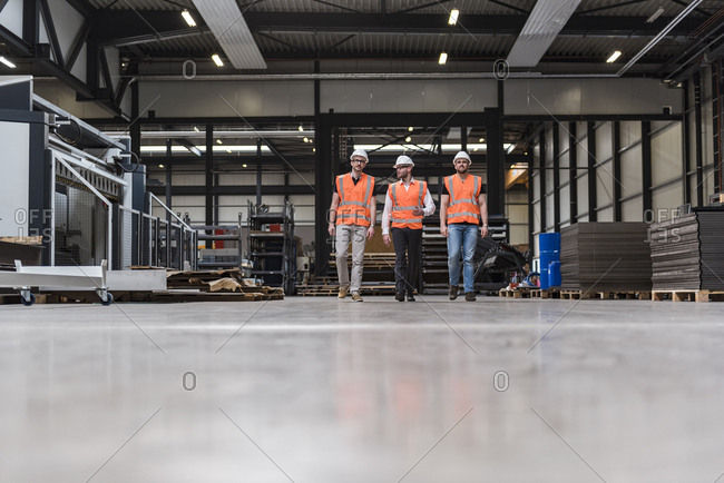 Three men wearing hard hats and safety vests walking on factory shop floor