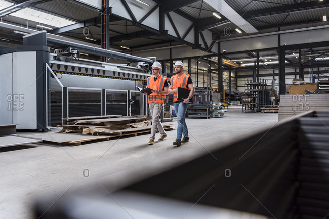 Two men wearing hard hats and safety vests walking on factory shop floor
