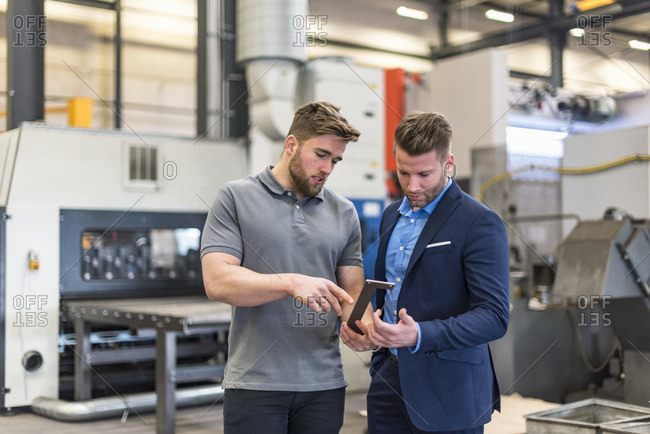 Employee explaining workpiece to businessman on factory shop floor