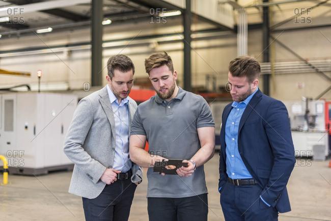 Employee explaining workpiece to businessmen on factory shop floor