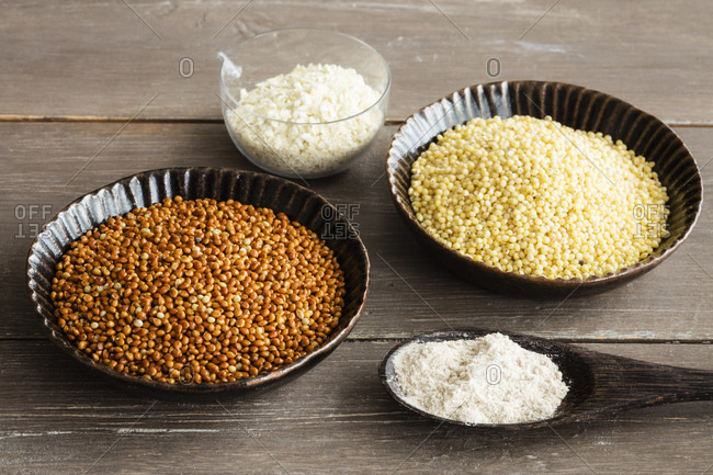 Spoons of Golden and brown millet- millet meal and millet flakes