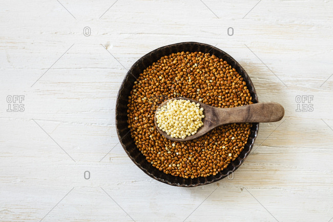 Bowl of brown millet and spoon of Golden millet
