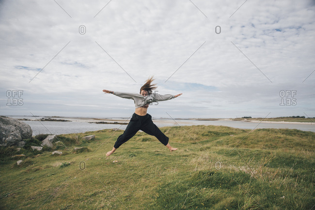 France- Brittany- Landeda- Dunes de Sainte-Marguerite- young woman jumping at the coast