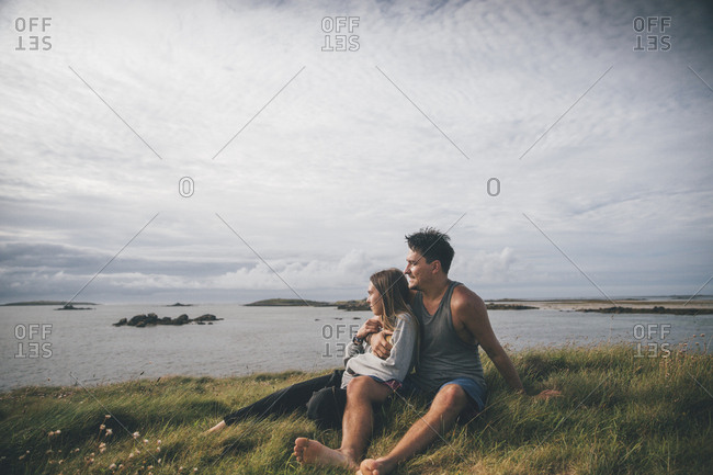 France- Brittany- Landeda- Dunes de Sainte-Marguerite- affectionate young couple sitting at the coast