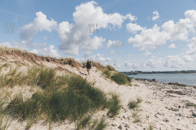 France- Brittany- Landeda- Dunes de Sainte-Marguerite- young woman walking in dune at the coast