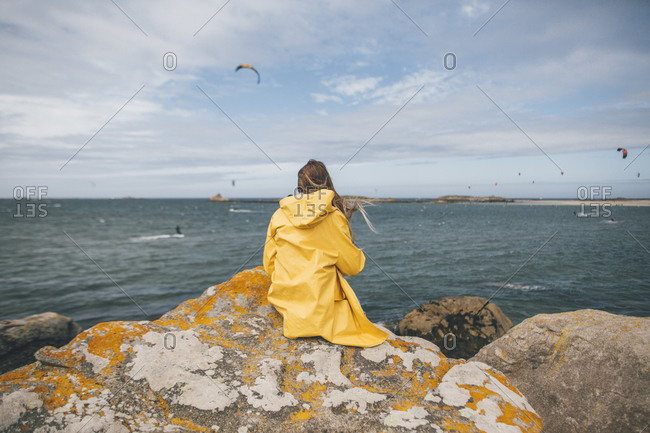France- Brittany- Landeda- Dunes de Sainte-Marguerite- young woman sitting on rock at the coast