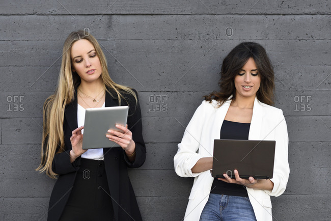 Two businesswomen using tablet and laptop