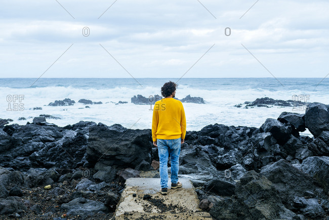 Azores- Sao Miguel- rear view of man looking at the sea from stony coast