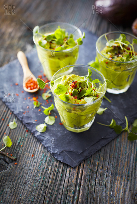 Glasses of avocado cream with chili flakes- cress and parsley