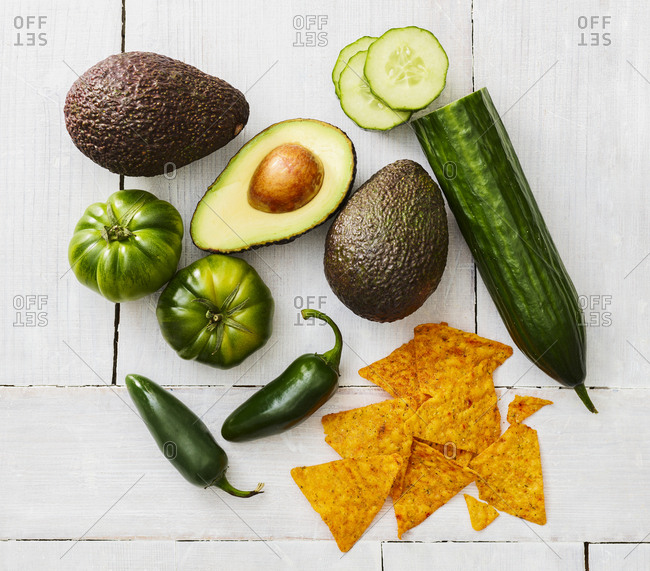 Sliced and whole avocado- green tomatoes- Jalapeno peppers- cucumber and tortilla chips