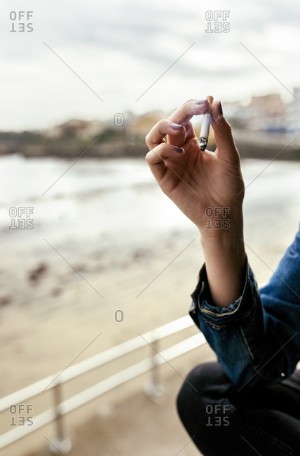Hand of a woman smoking a cigarette in a coastal village