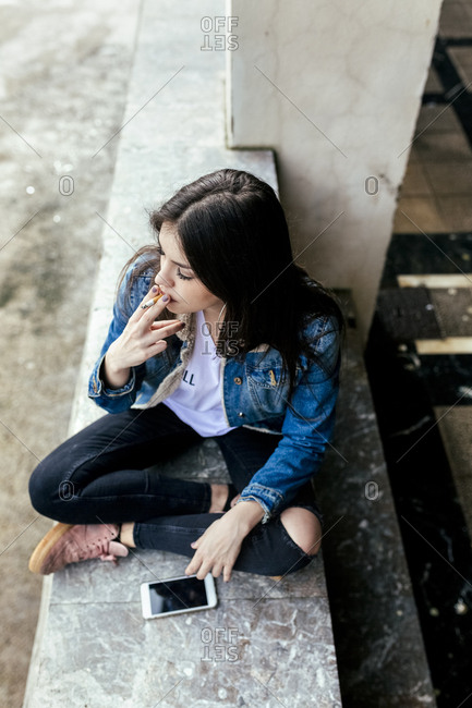 Young woman sitting on a wall smoking a cigarette
