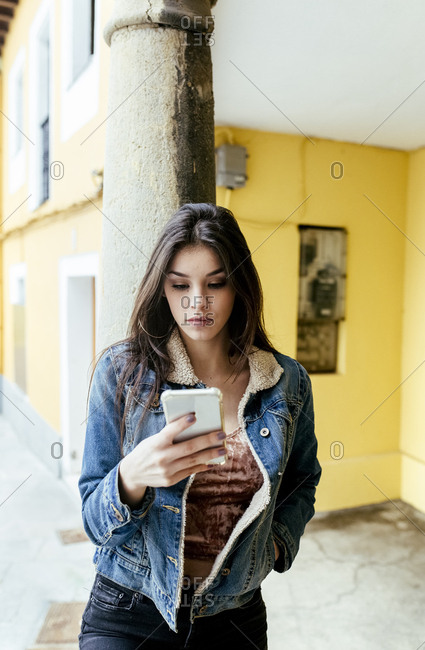 Young woman in a town checking her smartphone