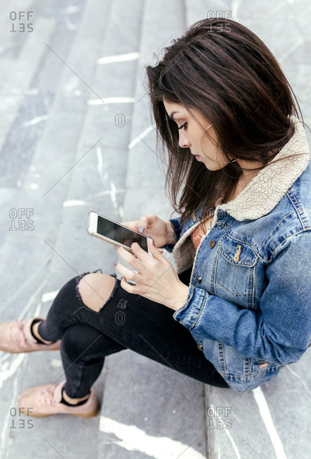 Young woman sitting on stairs checking her smartphone