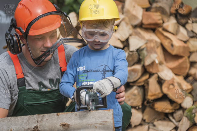 Father and son sawing wood together