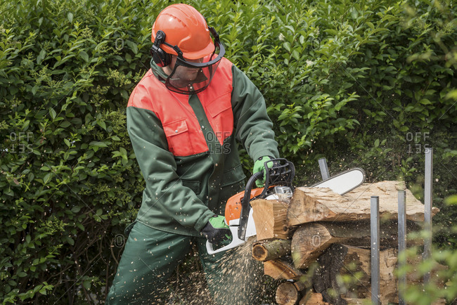 Man wearing protective clothes sawing wood with motor saw