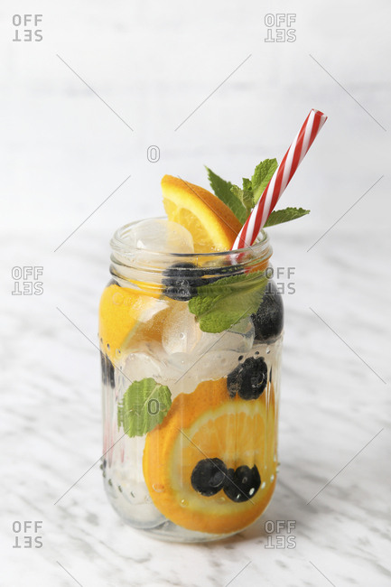 Glass of infused water with orange- blueberries and mint on ice