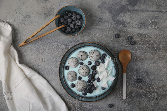 Blue smoothie bowl with grated coconut- blueberries and dragon fruit balls