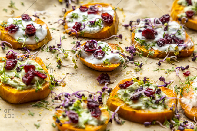 Slices of sweet potato with cream cheese- ramson cream- goat cheese- cress and cranberries