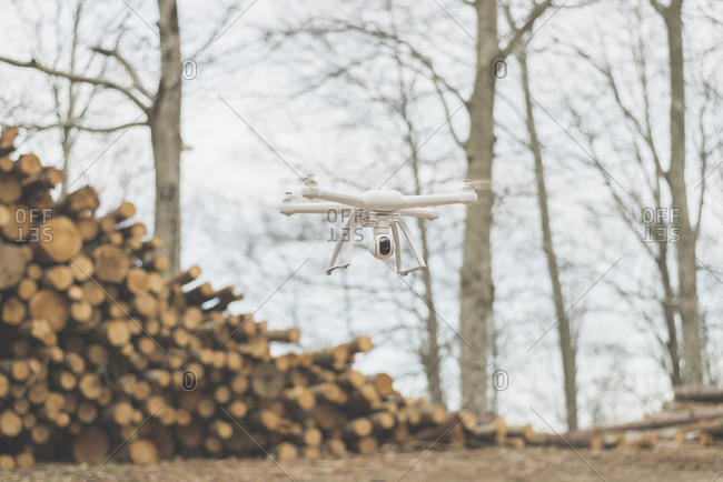A quadcopter drone flies near a stack of logs
