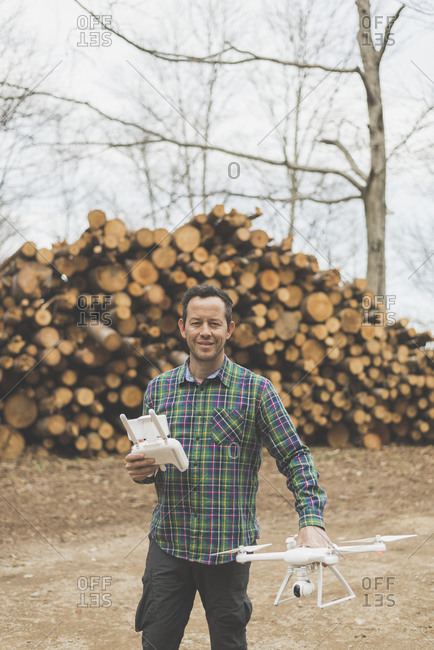 Man with a quadcopter drone beside a stack of logs