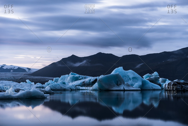 Icebergs and mountains reflected in still water
